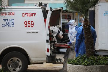 Magen David Adom workers wearing protective clothing, as a preventive measure against the coronavirus evacuating a woman with suspicion for Coronavirus at Hadassah Ein Karem hospital, in Jerusalem, on March 22, 2020. Photo by Flash90 *** Local Caption *** àç àçéí øåôà îðäì áéú äçåìéí áéú çåìéí äãñä äãñä òéï ëøí îçì÷ä îåãã çåí ëðñéä ùåîø îá÷ø åéøåñ ÷åøåðä øôåàä ôéðåé àéùä îáåâøú